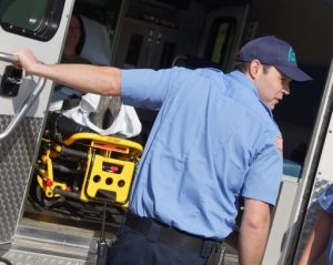 EMS worker holding ambulance door.
