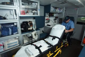 Paramedic in ambulance with empty stretcher