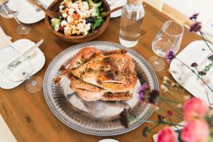 Turkey on a serving tray surrounded by thanksgiving foods and cutlery.