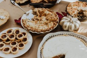 Thanksgiving foods like pie displayed on a dinner table.