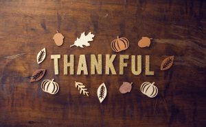 Cut out letters that spell Thankful laid out on a table surrounded by cut out leaves and pumpkins.